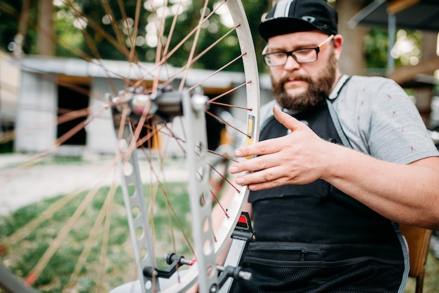 整備士が自転車のスポークと修理ホイールを調整します