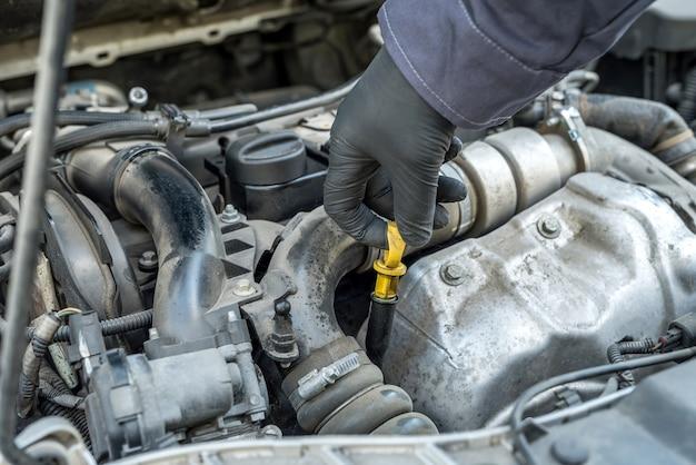 Механик после замены масла в двигателе проверяет уровень и качество по щупу. автосервис