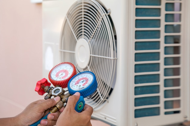 Mechanic air repair using manifold gauge for filling home air conditioner