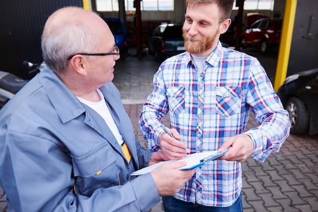 Механик и заказчик подписывают документ в мастерской