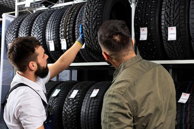 정비사와 고객이 수리 차고에서 타이어, 겨울 및 여름 타이어 교체에 대해 이야기합니다. 계절 타이어 교체 개념. 고객은 자신의 자동차에 가장 적합한 것을 선택합니다.