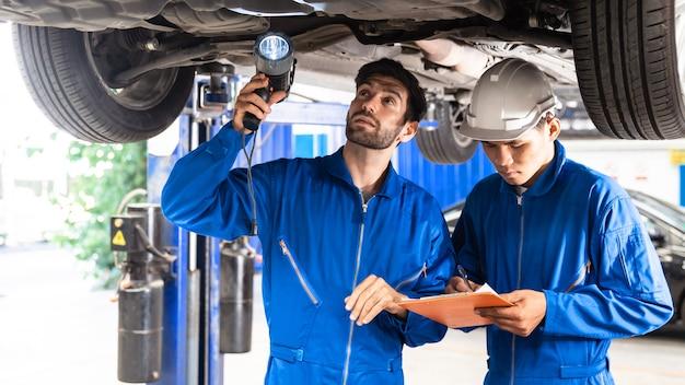 整備士と彼の助手がフラッシュライトで車の底を調べています。自動車修理サービスセンター。専門的なサービス。