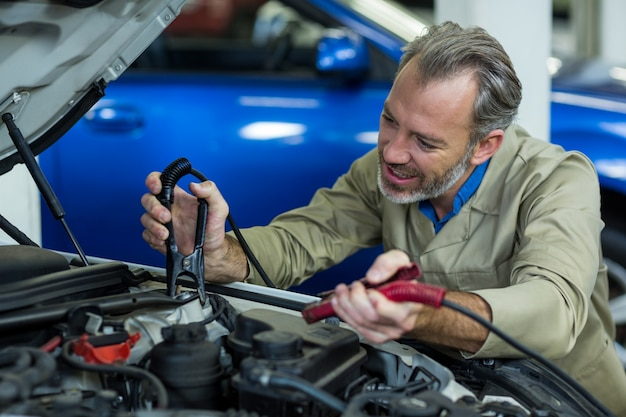 車のバッテリーにジャンパーケーブルを接続メカニック