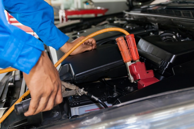 Mechanic attaching jumper cables with battery car