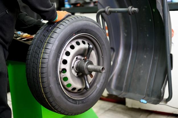 Mechanic balancing a car wheel.