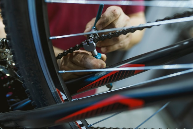 Mechanic in a bicycle repair shop fixing the chain of a bike