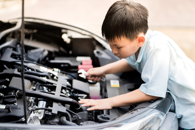 Mechanic boy working and repair car engine in car service centre. automobile metal car engine part details.