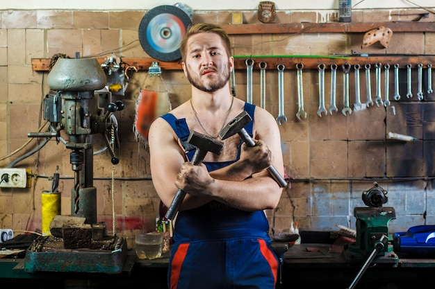 Mechanic in a car garage stands at the desktop with hammers in his hands.