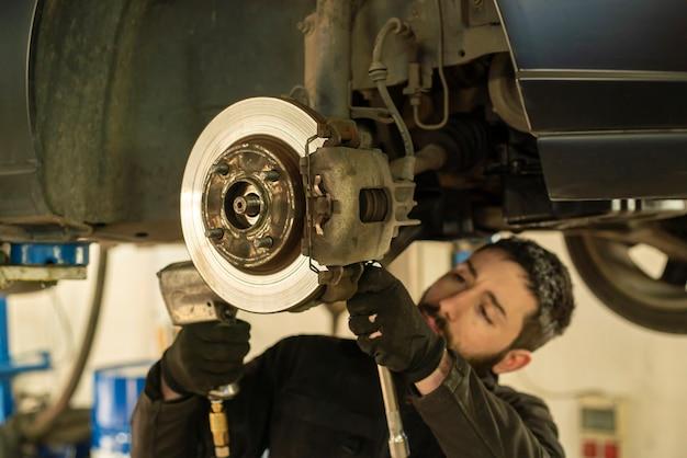정비사는 작업장에서 자동차 브레이크 교체를 수행합니다.