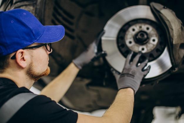 Meccanico che cambia i dischi dei freni nel servizio auto