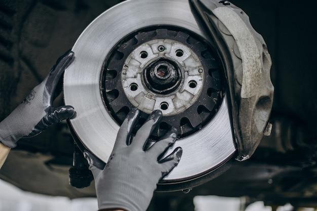 Механик меняет тормозные диски в автосервисе