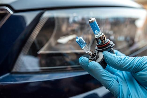 Mechanic changing car light bulb against headlight, auto service
