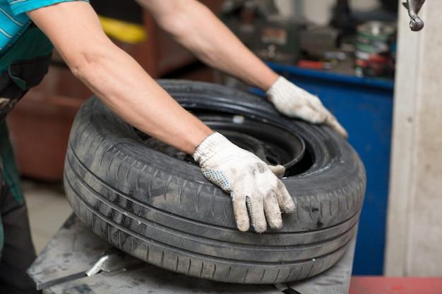 Механик меняет шиномонтаж автомобиля. ремонт колесных шин.