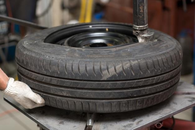 整備士が車のタイヤのフィッティングを交換します。ホイールタイヤの修理。