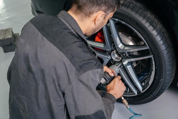 볼트 개념을 풀기 위해 전기 드릴을 사용하여 자동차 수리점에서 자동차 바퀴를 바꾸는 정비사