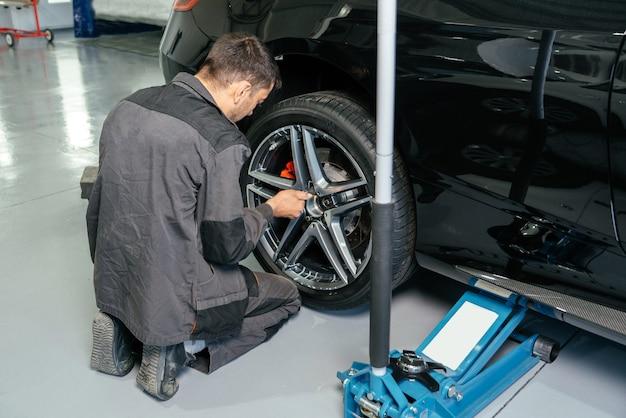 리프트 잭과 전기 드릴을 사용하여 자동차 수리점에서 자동차 휠을 교체하여 느슨하게 합니다.