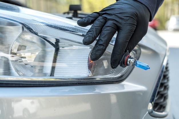 자동차 헤드 라이트의 새로운 할로겐 전구를 교체하는 정비공. 자동차 산업
