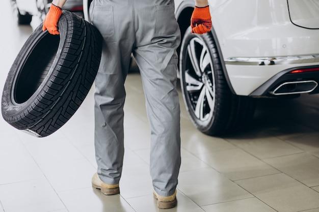 Механик меняет шины в автосервисе