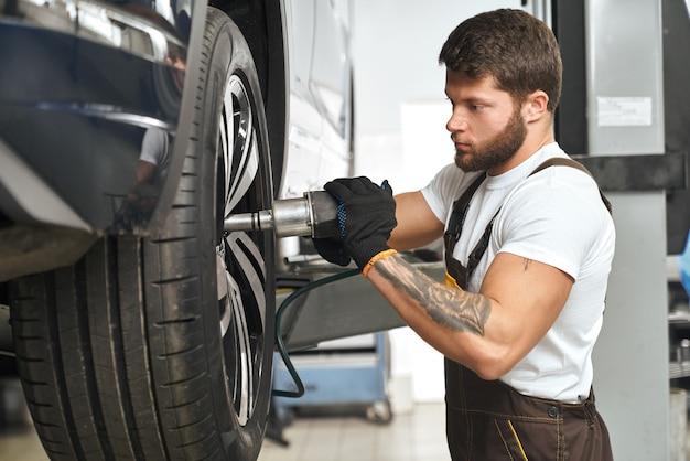 Mechanic changing wheel hubcap in automobile.