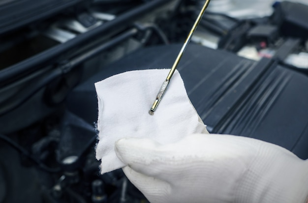 Mechanic checking engine oil level on car vehicle