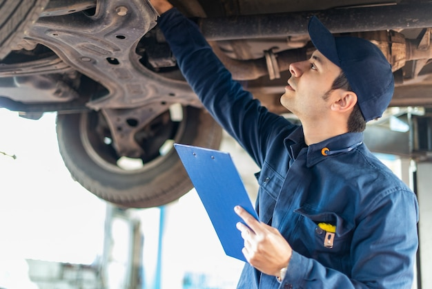 Mechanic checking a lifted car to make a quote