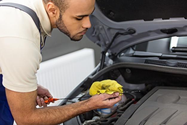 Механик, проверяющий уровень масла в двигателе с помощью щупа
