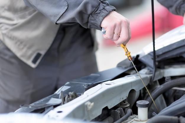 Механик проверяет уровень масла в двигателе автомобиля.