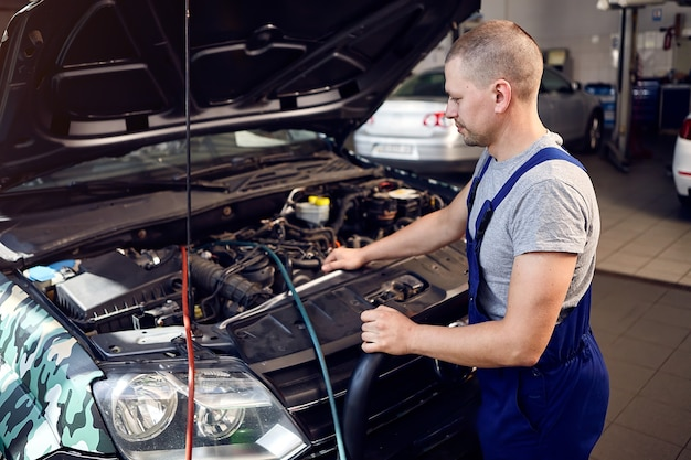 Mechanic checks air conditioning system in car auto service