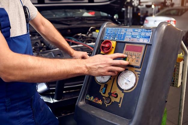 Механик проверяет систему кондиционирования воздуха в автосервисе