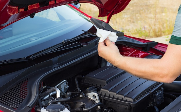 The mechanic checks the oil level in the car, the concept of the problem on the road