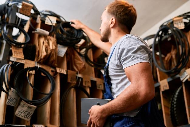 Mechanic choosing parts in storage room