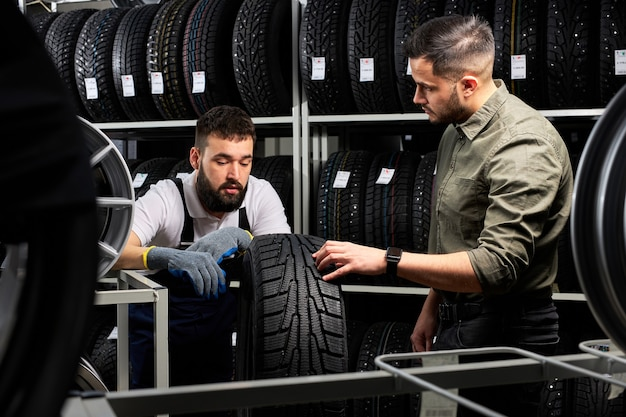 Mechanic and client checking tires in store, having conversation in shop, customer is going to make purchase