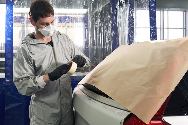 Mechanic covering car with paper before painting in auto repair service
