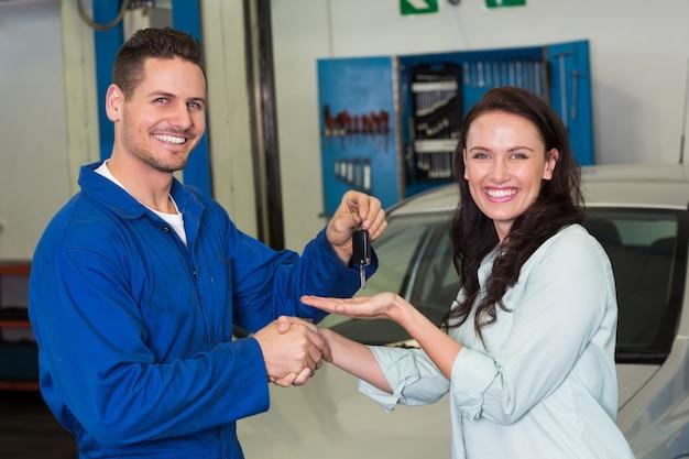 Mechanic and customer smiling at camera at the repair garage