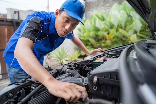 車のエンジンの検査を行う整備士