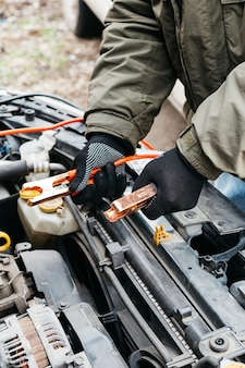 Mechanic engineer charging car battery with electricity using jumper cables outdoors. red and black jumper cables in male hands of car mechanic. man in gloves working in car repair service station.