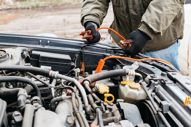 屋外でジャンパーケーブルを使用して車のバッテリーを電気で充電する整備士。