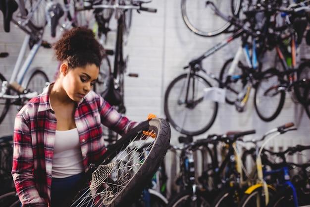 Механик осматривает велосипедное колесо