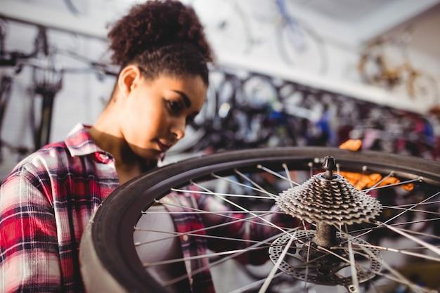 자전거 바퀴를 검사하는 정비공