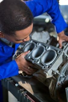 Механик осматривает части автомобиля