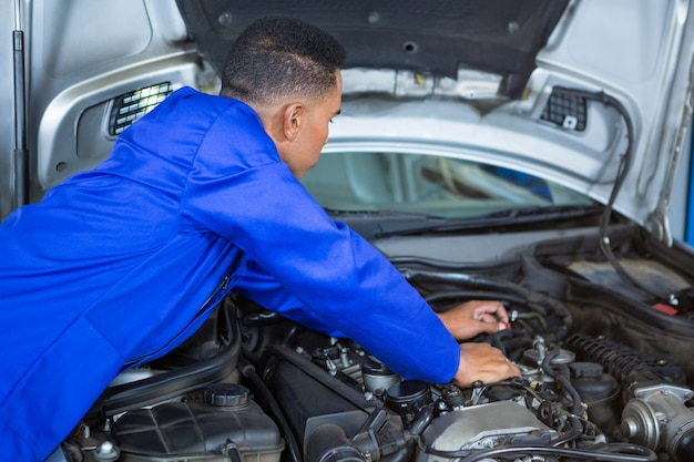 Mechanic examining car engine