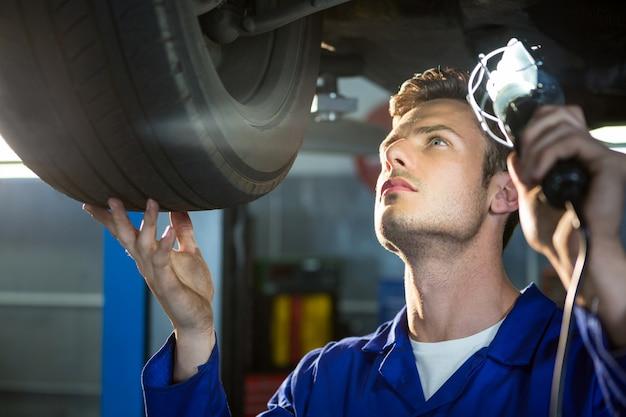 Mechanic examining car tyre using flashlight
