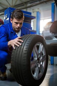 타이어를 검사하는 정비공