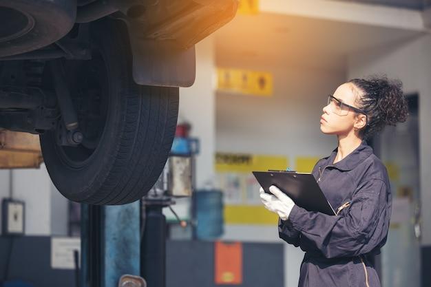 Mechanic examining underside at car service, auto repair service.