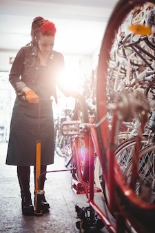 Mechanic filling air into bicycle tire with air pump