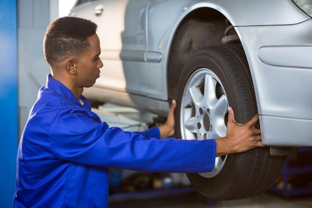 자동차 타이어를 고정하는 정비공