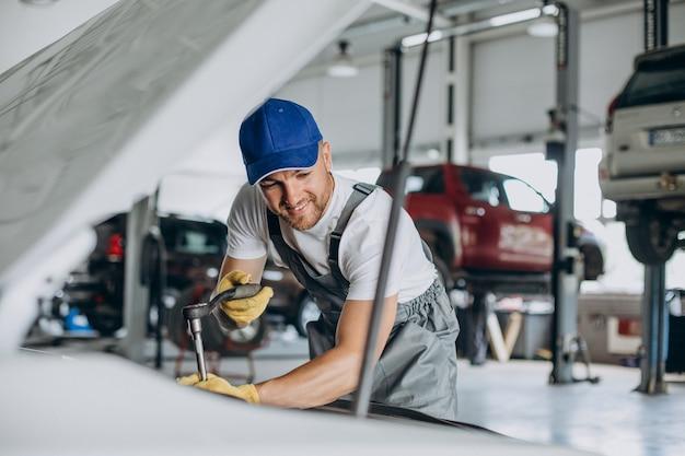 車のサービスステーションで車を修理する整備士