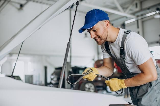Meccanico che ripara l'auto alla stazione di servizio dell'auto