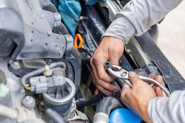 Mechanic fixing hose clamp with pliers tool cooling water pipe at car engine