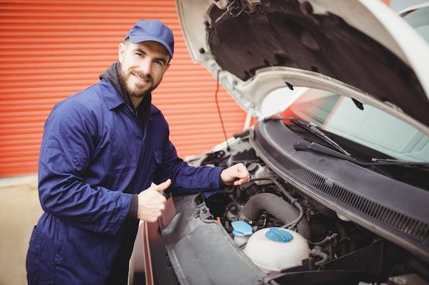 Mechanic fixing  a van with thumbs up